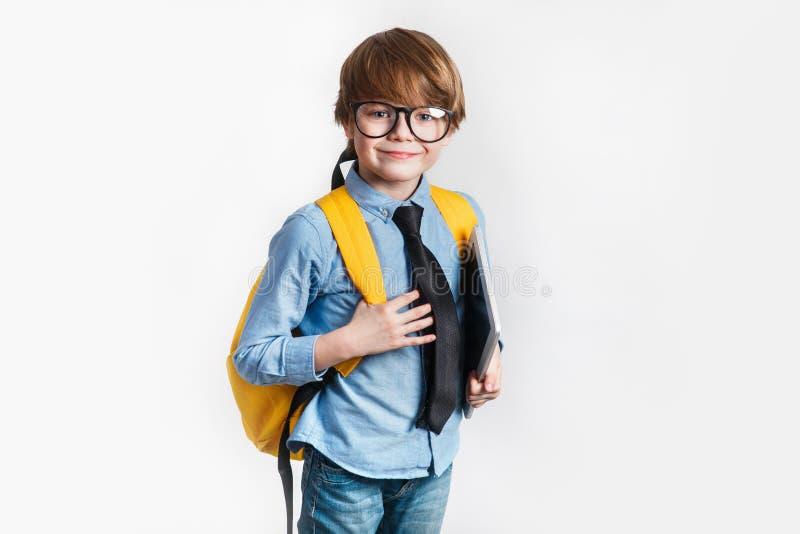 Lycklig gullig klyftig pojke i exponeringsglas med skolapåsen och minnestavla i hans hand tillbaka skola till arkivfoton