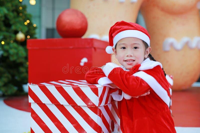 Lycklig gullig liten asiatisk barnflicka i den santa dräkten med gåvaasken nära julträd och bakgrund Julvinterferie royaltyfri fotografi