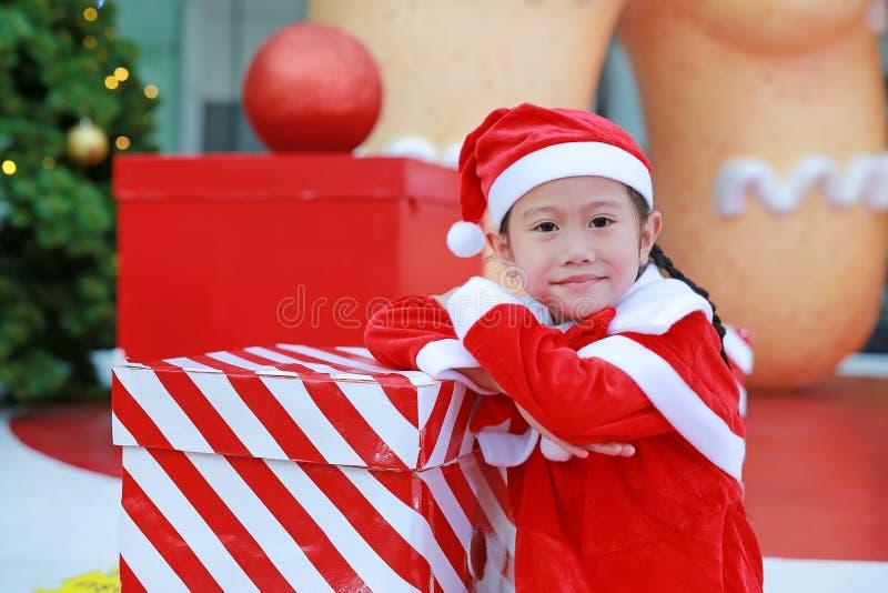 Lycklig gullig liten asiatisk barnflicka i den santa dräkten med gåvaasken nära julträd och bakgrund Julvinterferie royaltyfri bild