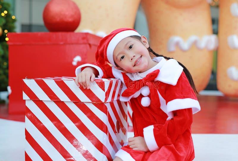 Lycklig gullig liten asiatisk barnflicka i den santa dräkten med gåvaasken nära julträd och bakgrund Julvinterferie lurar arkivfoto