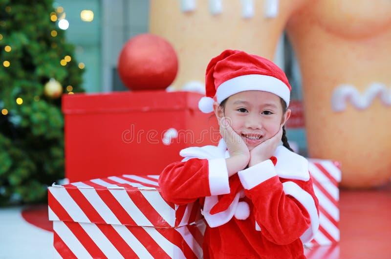Lycklig gullig liten asiatisk barnflicka i den santa dräkten med gåvaasken nära julträd och bakgrund Julvinterferie lurar arkivfoton