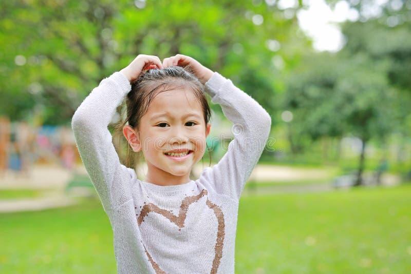 Lycklig gullig liten asiatisk barnflicka i grön trädgård med framställning av hennes händer för hjärtatecken arkivfoto