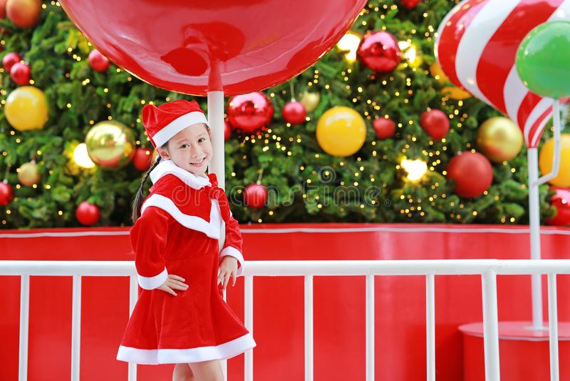 Lycklig gullig liten asiatisk barnflicka i jultomtendräkt nära julgranen och bakgrund Begrepp för julvinterferie fotografering för bildbyråer