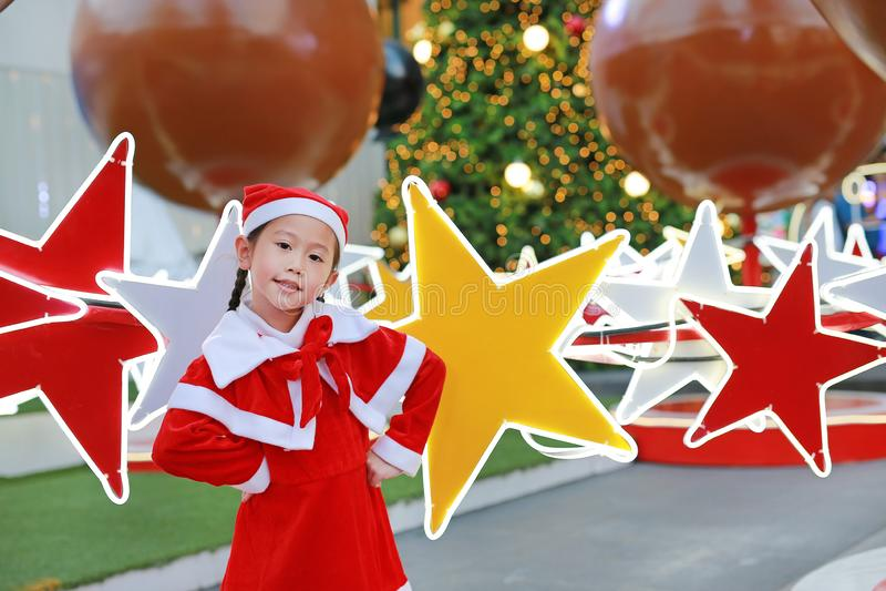 Lycklig gullig liten asiatisk barnflicka i jultomtendräkt nära julgranen och bakgrund Begrepp för julvinterferie arkivbild