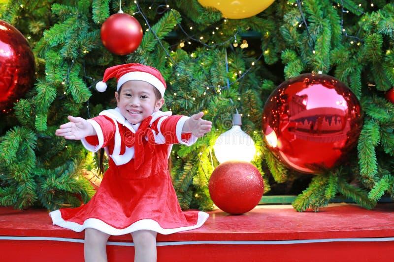 Lycklig gullig liten asiatisk barnflicka i jultomtendräkt nära julgranen och bakgrund Begrepp för julvinterferie arkivbilder