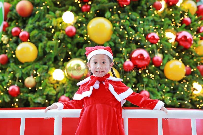 Lycklig gullig liten asiatisk barnflicka i jultomtendräkt nära julgranen och bakgrund Begrepp för julvinterferie royaltyfri foto