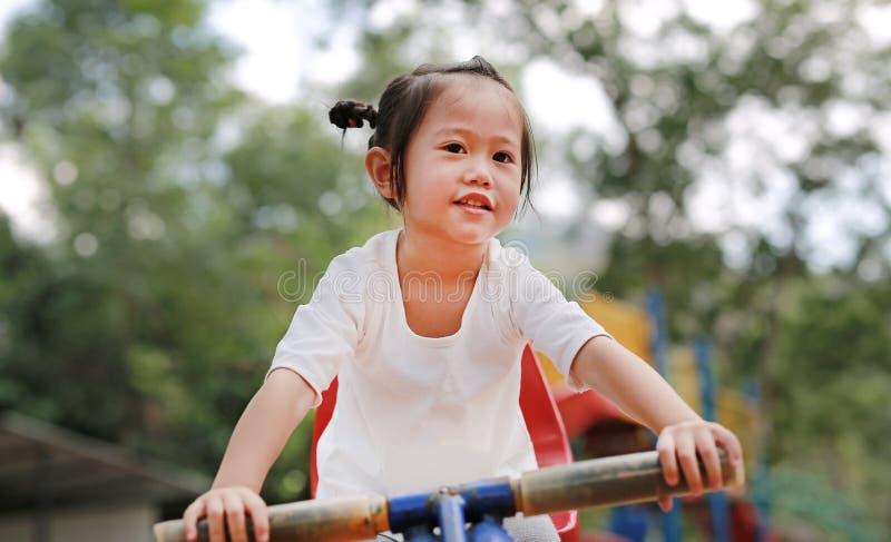 Lycklig gullig liten flicka på se-sågen i parkera royaltyfria bilder
