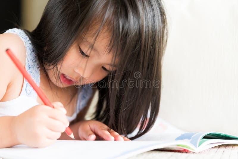 Lycklig gullig liten flicka som ler och rymmer den röda blyertspennan arkivbilder