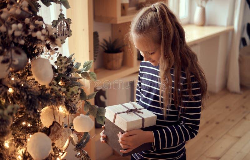 Lycklig gullig liten flicka som rymmer julgåvaasken royaltyfri bild