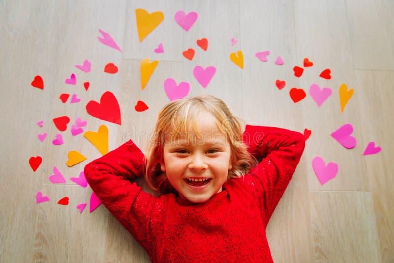 Lycklig gullig liten flickalek med hjärtor från papper, valentindag royaltyfri bild