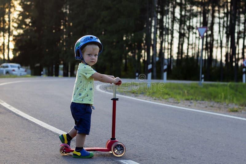 Lycklig gullig pojke på sparksparkcykeln i parkera kopiera avstånd Begrepp av sporten och sunt liv royaltyfri bild