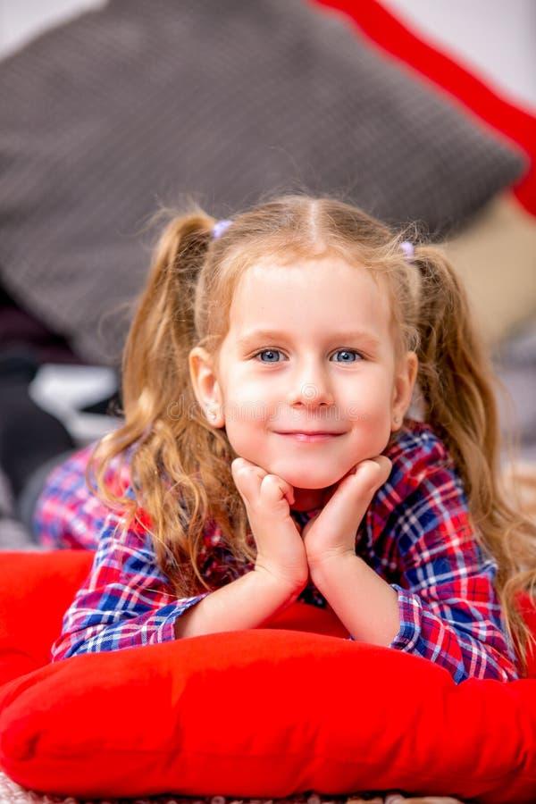 Lycklig gullig ung flicka i en rutig blått-röd klänning som ligger på sängen och le arkivbild