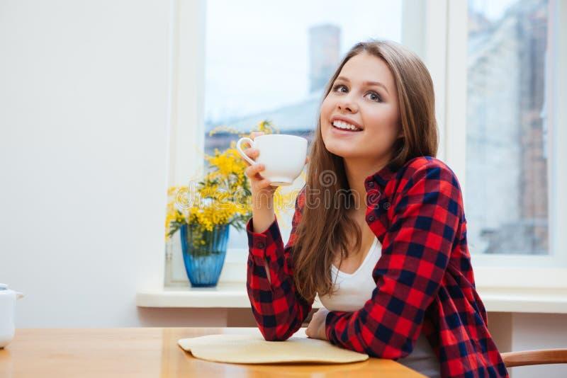 Lycklig gullig ung kvinna som hemma dricker coffe på kök royaltyfri foto