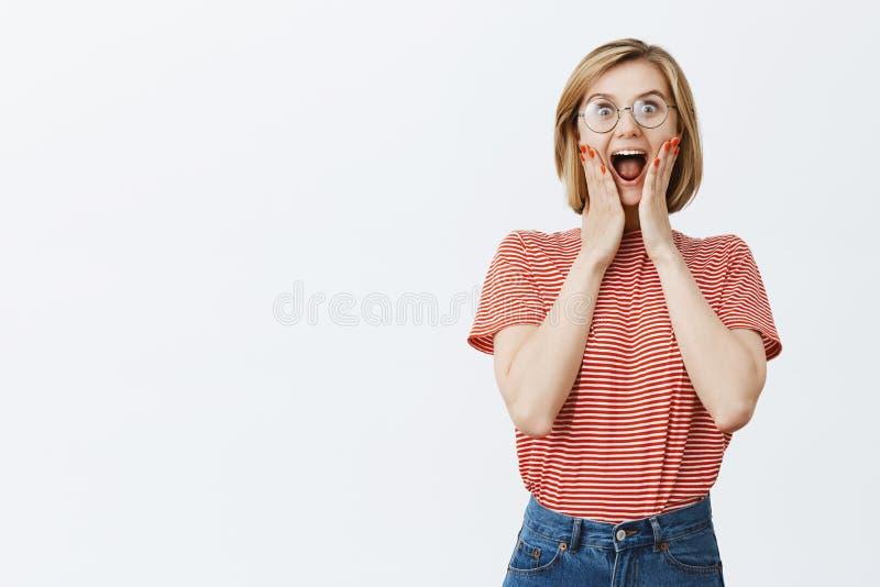 Lycklig hänförd och glad kvinnlig fan med blont hår i exponeringsglas och att skrika från glädje och spänningen som rymmer på hän arkivfoton