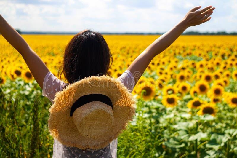Lycklig härlig asiatisk kvinna med sugrörhatten i solrosfält royaltyfri bild