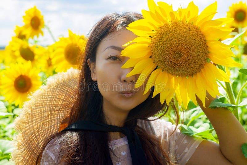 Lycklig härlig asiatisk kvinna med sugrörhatten i solrosfält royaltyfria foton