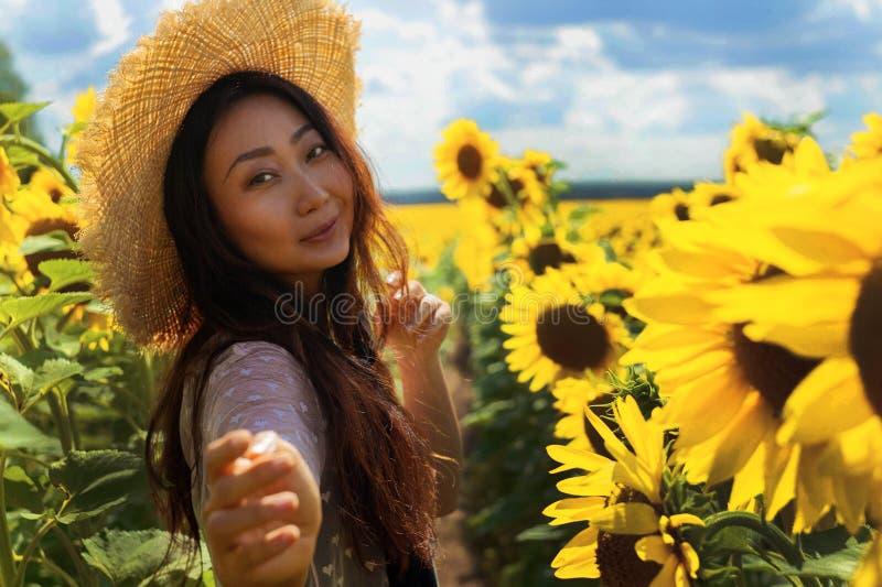 Lycklig härlig asiatisk kvinna med sugrörhatten i solrosfält arkivfoto
