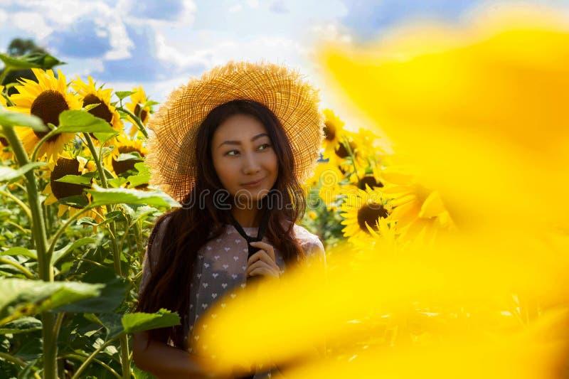 Lycklig härlig asiatisk kvinna med sugrörhatten i solrosfält royaltyfri foto