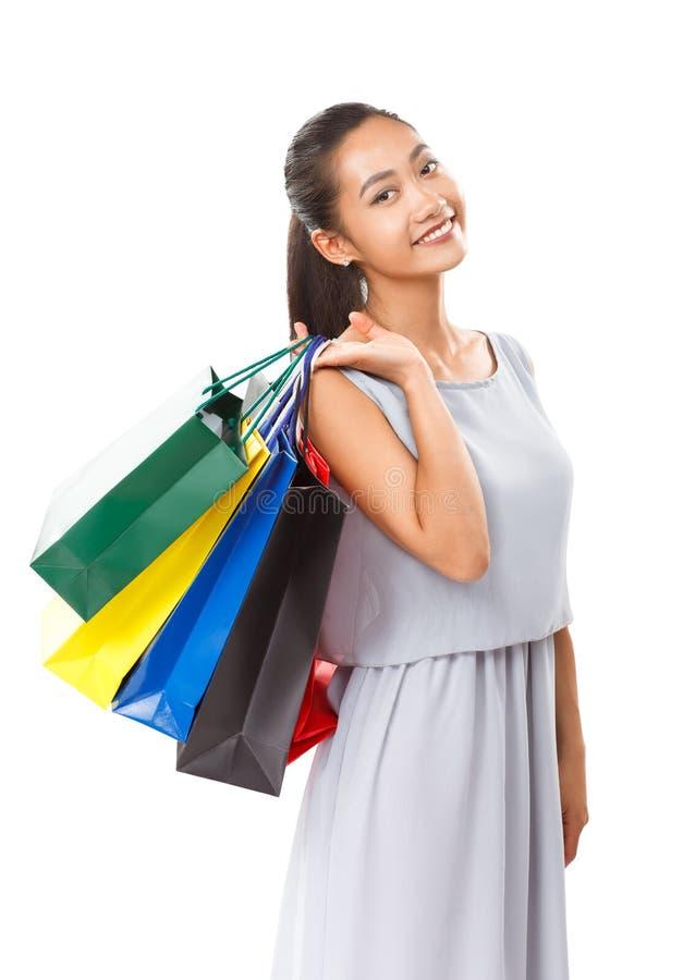 Lycklig härlig asiatisk kvinna som rymmer många färgrika shoppingpåsar royaltyfria bilder
