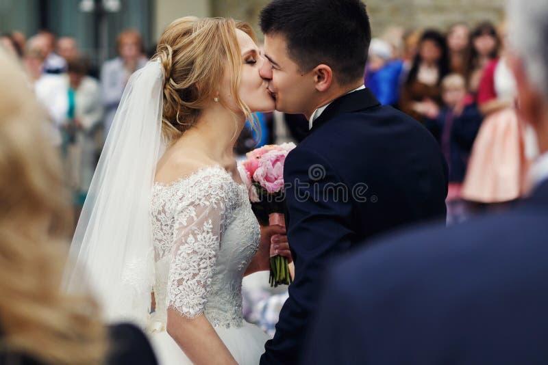 Lycklig härlig blond brud som kysser stiliga le brudgumclos royaltyfri foto