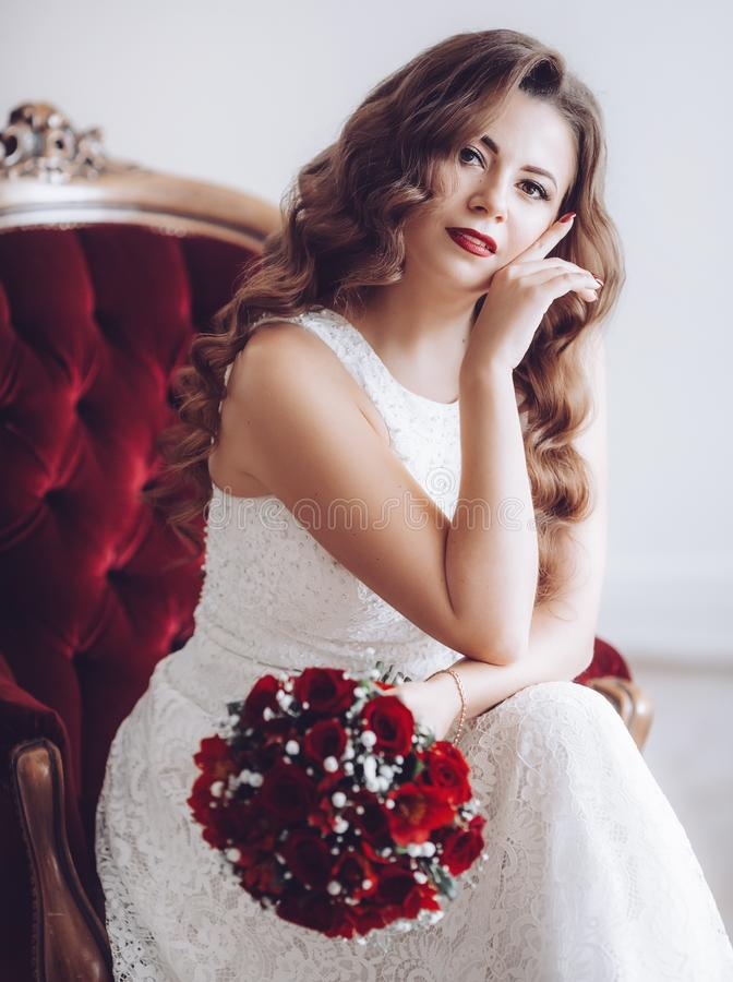Lycklig härlig brud i den vita klänningen med röda rosor arkivbild