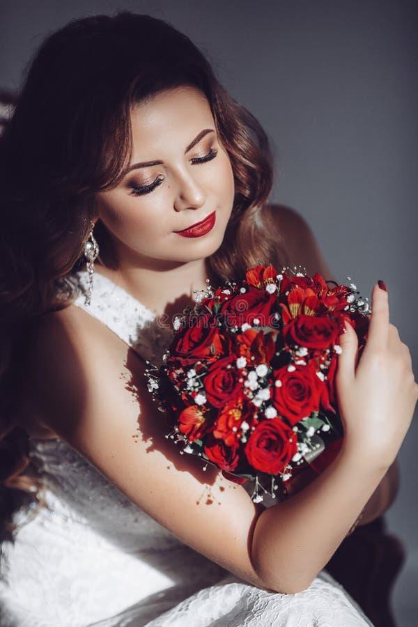 Lycklig härlig brud i den vita klänningen med röda rosor arkivfoton