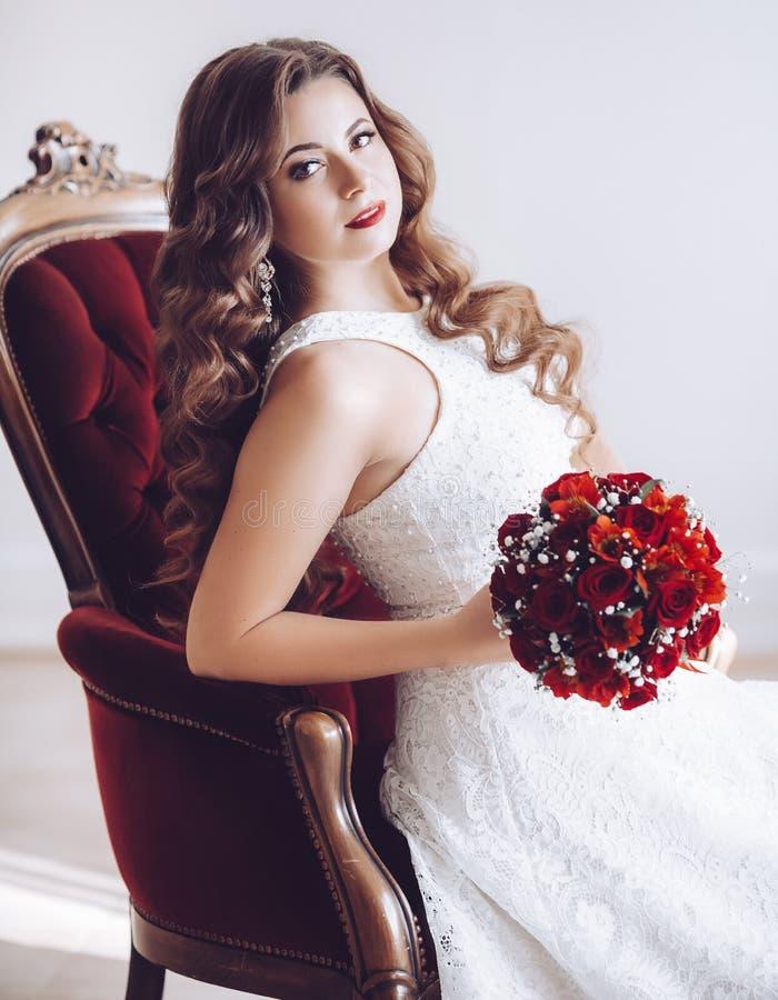 Lycklig härlig brud i den vita klänningen med röda rosor royaltyfria bilder