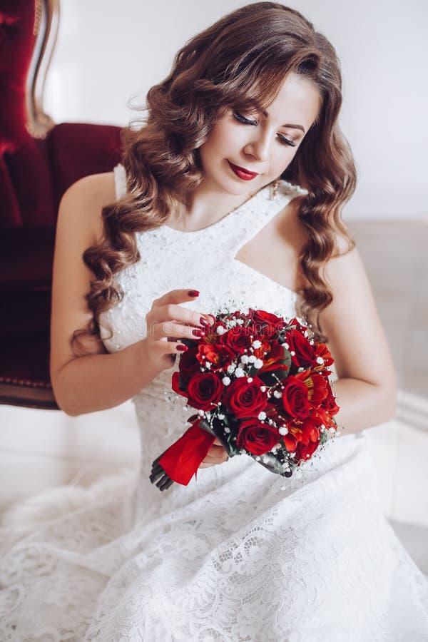 Lycklig härlig brud i den vita klänningen med röda rosor royaltyfri foto