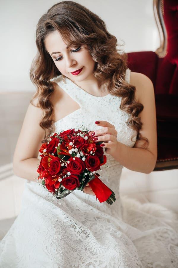 Lycklig härlig brud i den vita klänningen med röda rosor royaltyfri bild