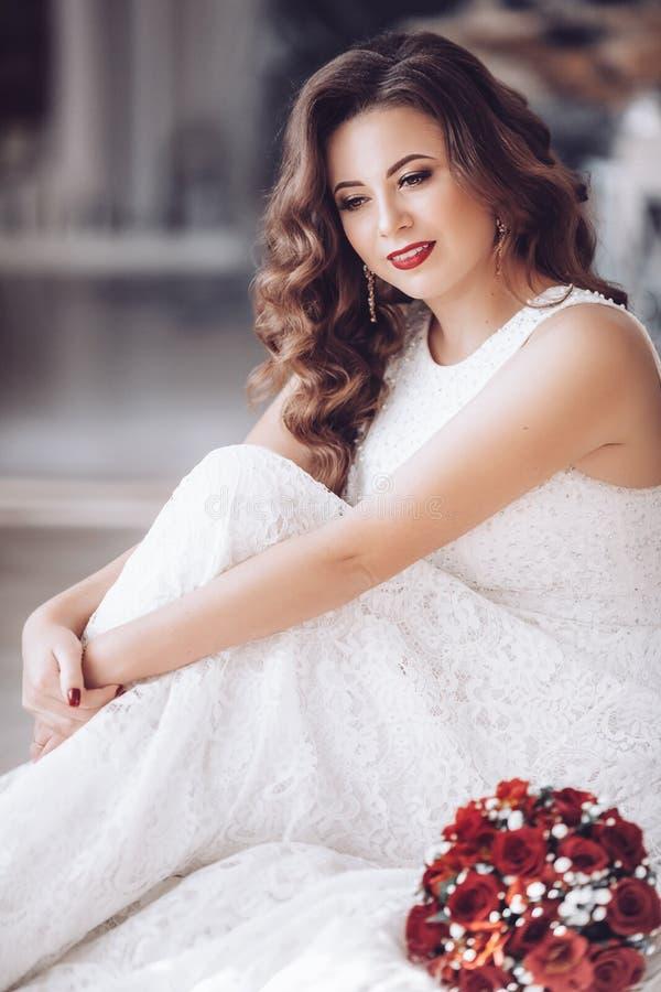 Lycklig härlig brud i den vita klänningen med röda rosor arkivfoto