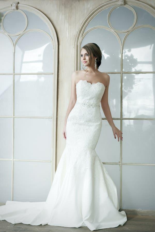 Lycklig härlig brudflicka i den vita klänningen för bröllop royaltyfria bilder