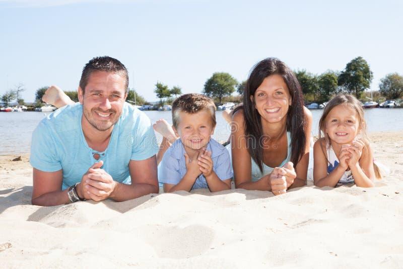 Lycklig härlig familj med ungar som tillsammans ligger på den europeiska atlantiska stranden under sommarsemester arkivbild
