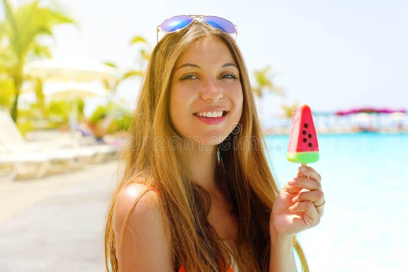 Lycklig härlig flicka som äter isglassispop i form av vattenmelonskivan och ser kameran Sommaren semestrar begrepp royaltyfria foton