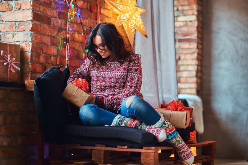 Lycklig härlig flicka som tycker om julmorgon, medan sitta på en soffa med gåvaaskar i ett dekorerat rum med vinden fotografering för bildbyråer