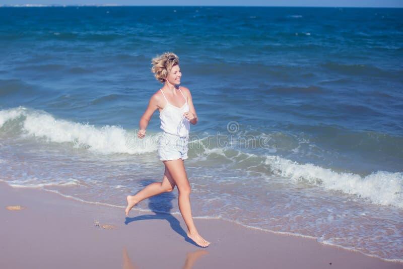Lycklig härlig fri kvinnaspring på hoppa för strand som är skämtsamt royaltyfri foto