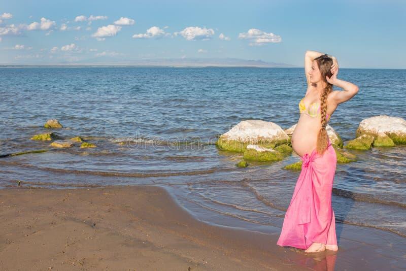 Lycklig härlig gravid kvinna, i att gå för baddräkt royaltyfri fotografi