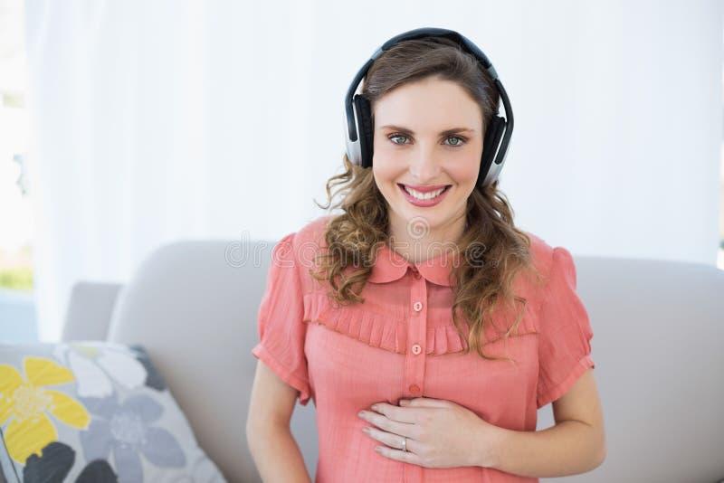 Lycklig härlig gravid kvinna som kopplar av i vardagsrummet som lyssnar till musik arkivfoto