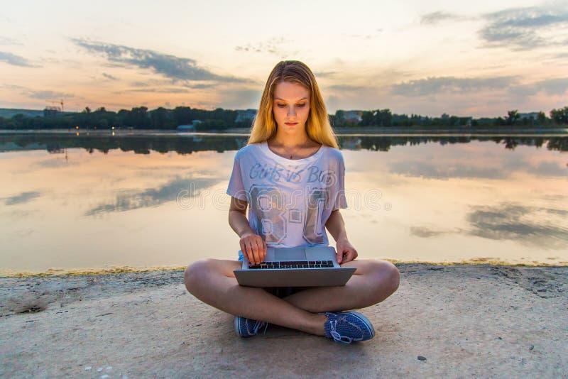 Lycklig härlig kvinna, flicka med bärbara datorn som nära surfar rengöringsduken vid sjön royaltyfri bild