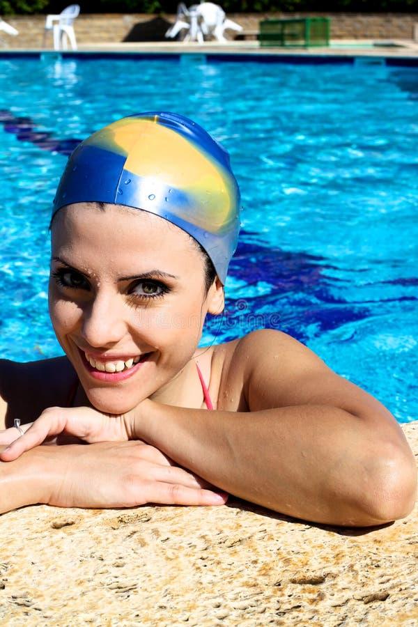 Lycklig härlig kvinna i simbassäng med att le för lock royaltyfria foton