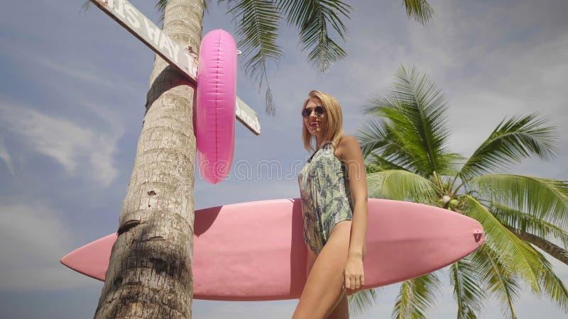Lycklig härlig kvinna med den rosa surfingbrädan som går till stranden arkivbild