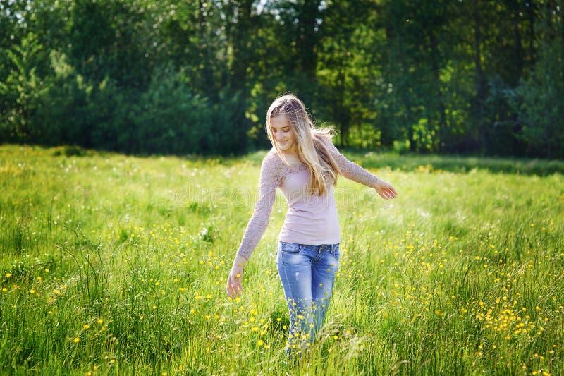 Lycklig härlig kvinna som går på en våräng arkivfoton