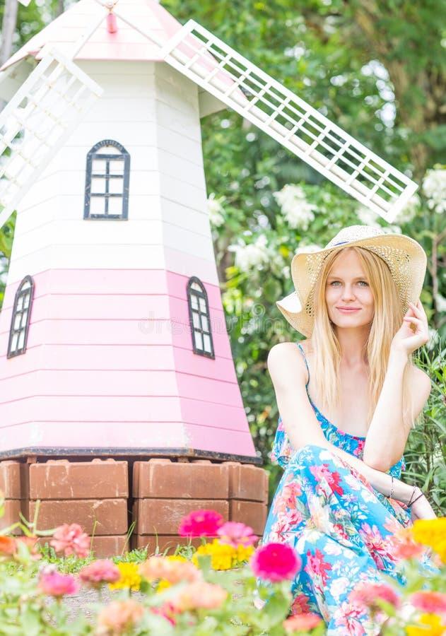 Lycklig härlig kvinna som sitter i en blommaträdgård royaltyfri bild
