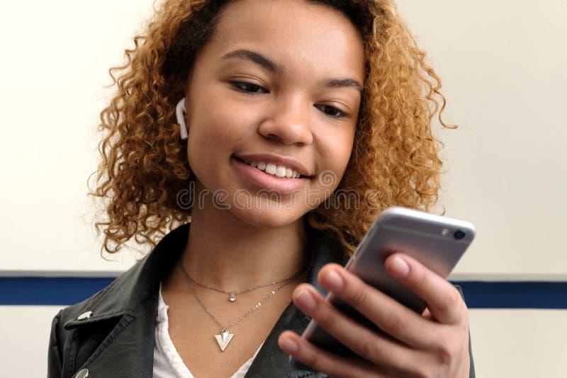 Lycklig härlig mörkhyad flicka som ser in i telefonen En trådlös skalm i örat av en ung kvinna för afrikansk amerikan arkivbild