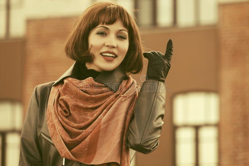 Lycklig härlig modekvinna i brunt halsduk- och läderlag i stadsgata royaltyfria bilder
