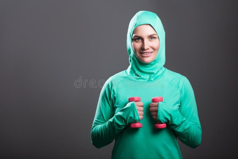 Lycklig härlig muslimkvinna i grön hijab eller islamisk sportswea royaltyfri bild