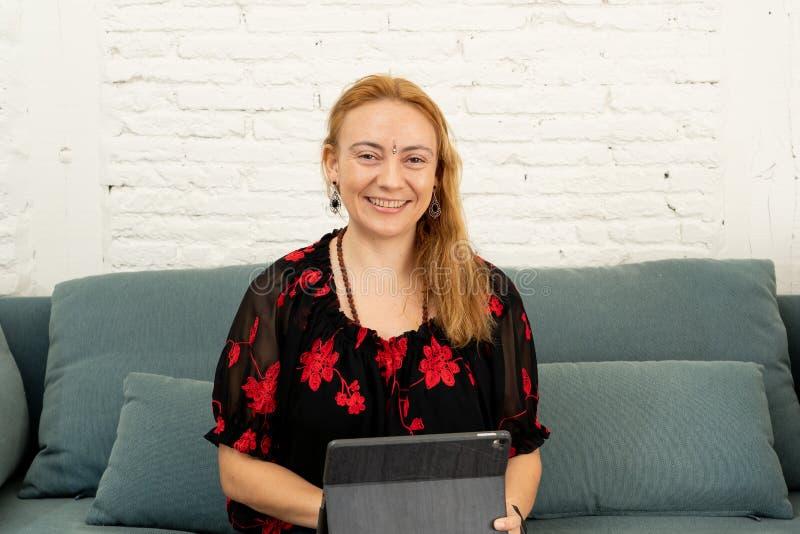 Lycklig härlig säker frilans- kvinna som hemma arbetar med minnestavlan på hennes online-nya företag arkivfoton