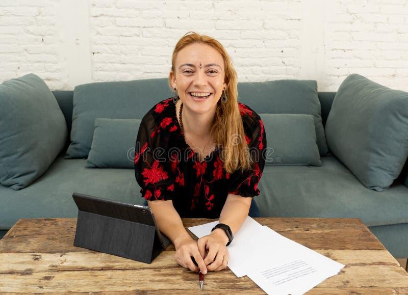 Lycklig härlig säker frilans- kvinna som hemma arbetar med minnestavlan på hennes online-nya företag arkivbild