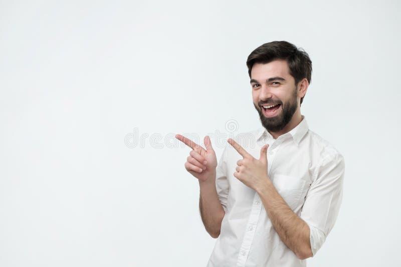 Lycklig härlig skäggig grabb som ser kameran, åt sidan ler och pekar med handen royaltyfria bilder