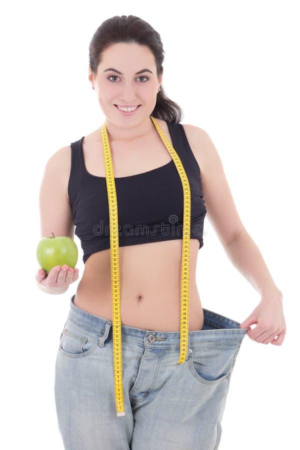 Lycklig härlig slank kvinna i stor jeans med äpplet och att mäta royaltyfri foto