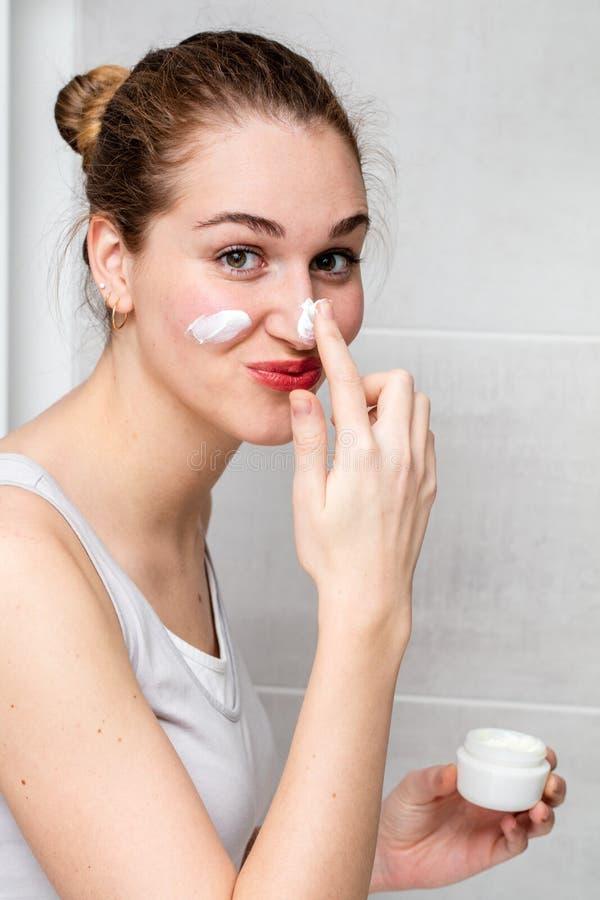 Lycklig härlig tonårs- flicka som trycker på hennes näsa med framsidakräm royaltyfri fotografi